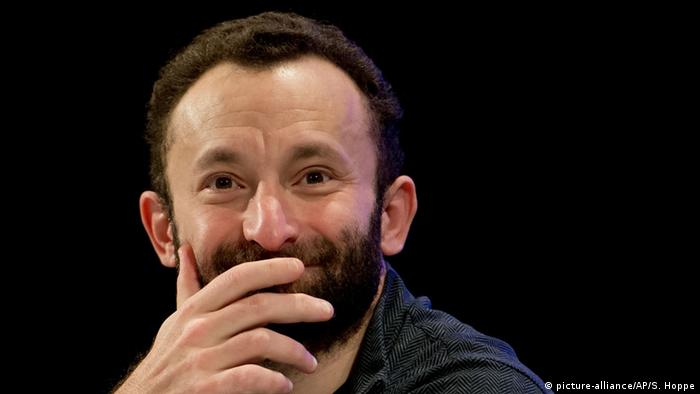Kirill Petrenko smiling broadly, partially covering his face with his hand