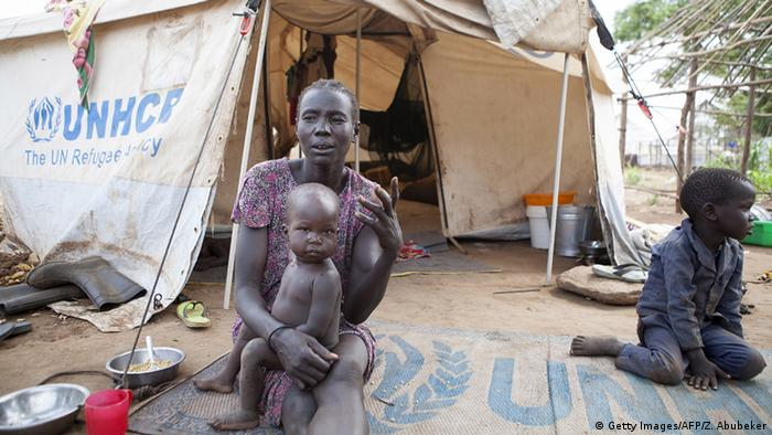 A woman with her child outside a UNHCR tent at a refugee camp