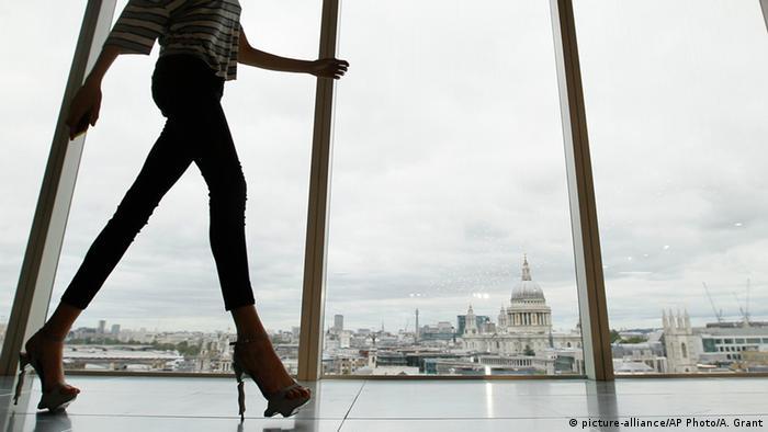 A woman wearing skinny jeans walks down a hallway