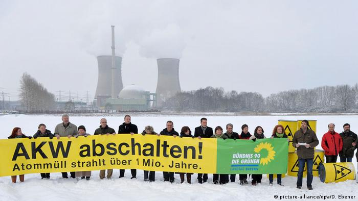 Green politicians holding protest sign in front of Grafenrheinfeld nuclear plant (Photo: David Ebener/dpa)