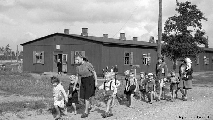 Children being led along a path outside a refugee shelter in northern Germany after the war (picture-alliance/akg)