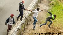 A police officer sprays tear gas to migrants trying to access the Channel Tunnel on the A16 highway on June 23, 2015 in Calais, northern France. AFP PHOTO PHILIPPE HUGUEN (Photo credit should read PHILIPPE HUGUEN/AFP/Getty Images)