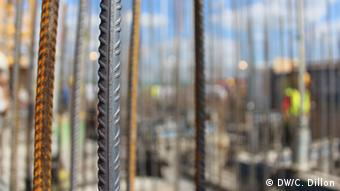 Rebar in the foreground of an ongoing construction project.