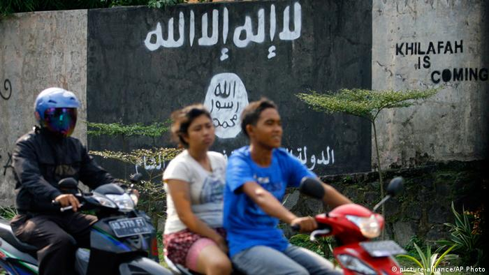 Motorists ride past a graffiti of the Islamic State group's flag in Solo, Central Java, Indonesia (AP Photo)