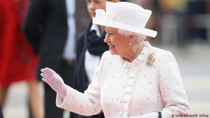 Queen Elizabeth II wearing white and waving at a crowd