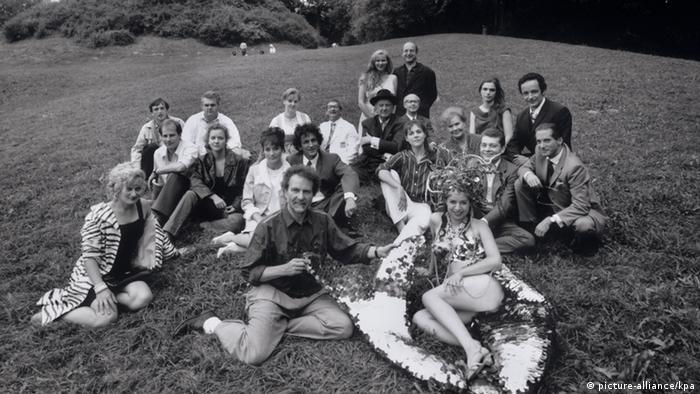 Filmteam um Edgar Reitz' Die zweite Heimat, Regisseur und Schauspieler und Teammitglieder sitzend im Englischen Garten (picture-alliance/kpa)
