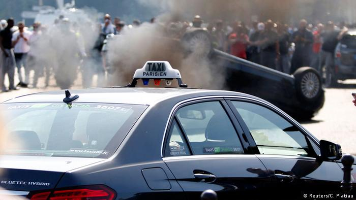 An overturned car is pictured as French taxi drivers, who are on strike, demonstrate at Porte Maillot to block the traffic on the Paris ring road during a national protest against car-sharing service Uber, in Paris, France, June 25, 2015 (Photo: REUTERS/Charles Platiau)