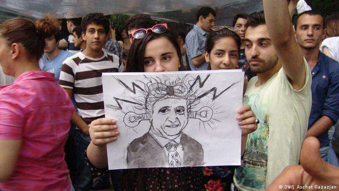 Женщина держит в руках плакат с шаржем на президента Армении