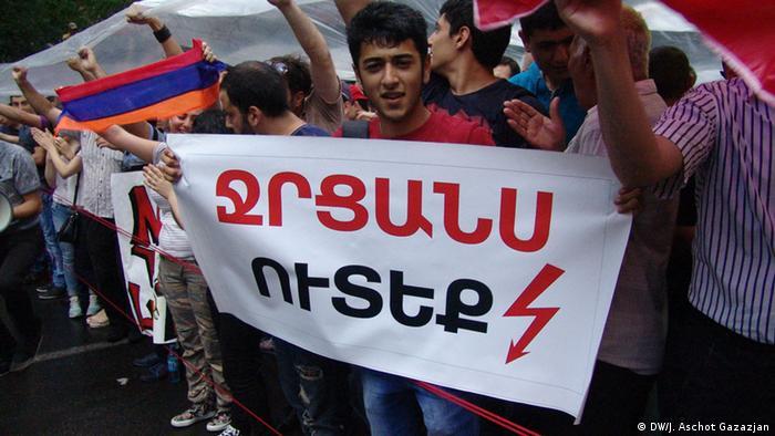 Юноша держит в руках плакат с надписью Съешьте мой водомет на армянском языке