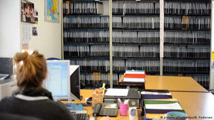 An employee works looking at shelves full of files on asylum-seekers (picture-alliance/dpa/B. Pedersen)