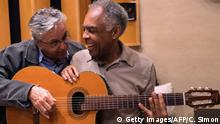 Brazilian musicians Caetano Veloso (L) and Gilberto Gil play the same guitar at Gil's music studio in Rio de Janeiro, Brazil on June 15, 2015. AFP PHOTO / CHRISTOPHE SIMON (Photo credit should read CHRISTOPHE SIMON/AFP/Getty Images)