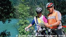 Couple of cyclists looking at a map with a river in the background