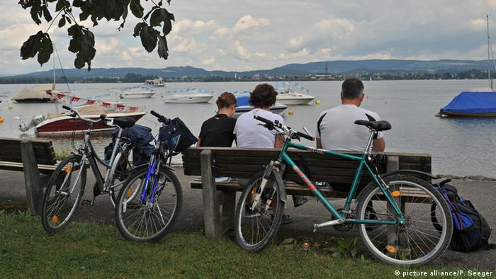 Three cyclists sitting on a bench looking out over Lake Constance with its boats