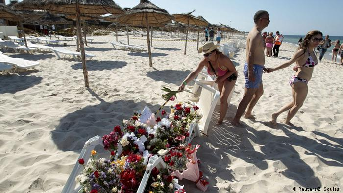 A tourist places flowers at the beachside of the Imperiale Marhabada hotel, which was attacked by a gunman in Sousse, Tunisia, June 26, 2015.
