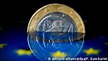 ARCHIV - ILLUSTRATION - Eine griechische Euro-Münze spiegelt sich am 13.03.2015 in Düsseldorf (Nordrhein-Westfalen) im Wasser. Foto: Federico Gambarini/dpa (zu dpa: Kapitalkontrollen, Pleite, Grexit - Szenarien für Griechenland vom 28.06.2015) +++(c) dpa - Bildfunk+++