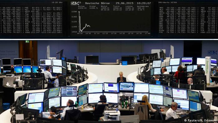 Traders sit at their desks in front of the DAX board at the Frankfurt stock exchange