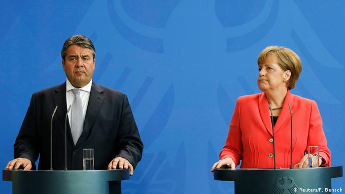 German Foreign Minister Sigmar Gabriel delivers a press conference next to German Chancellor Angela Merkel