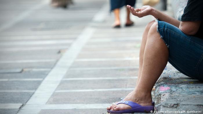 এথেন্সের রাজপথে ভিক্ষার আশায় হাত বাড়িয়ে রয়েছেন এক নারী