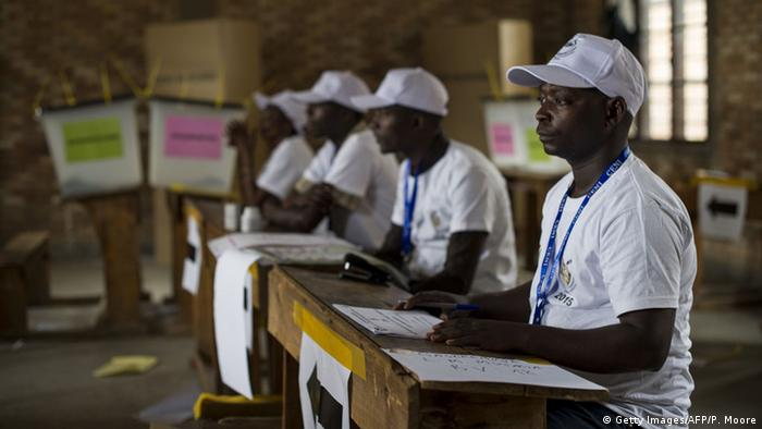 Election helpers wait at an empty polling station in Bujumbura