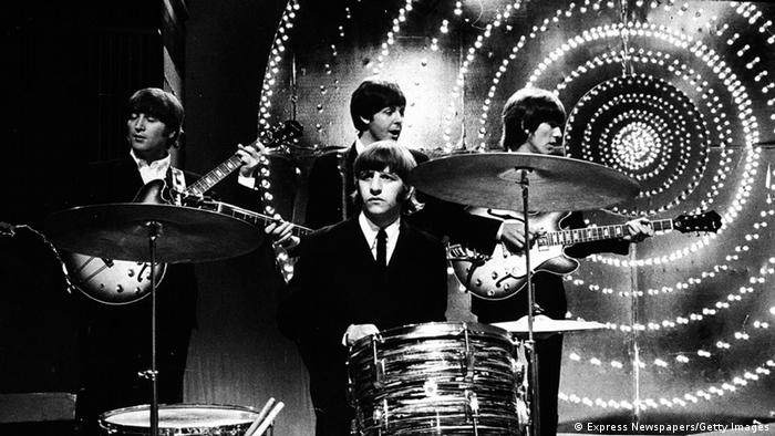 British rock group The Beatles perform live on stage in front of a circular lit backdrop at the BBC TV Centre, June 1966. L-R: Guitarist John Lennon (1940 - 1980), drummer Ringo Starr, singer and bassist Paul McCartney and guitarist George Harrison (1943 - 2001).