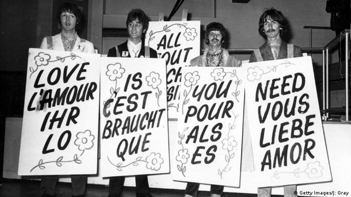 The Beatles sporting multi-lingual 'Love Is All You Need' sandwich boards at the EMI studios in Abbey Road