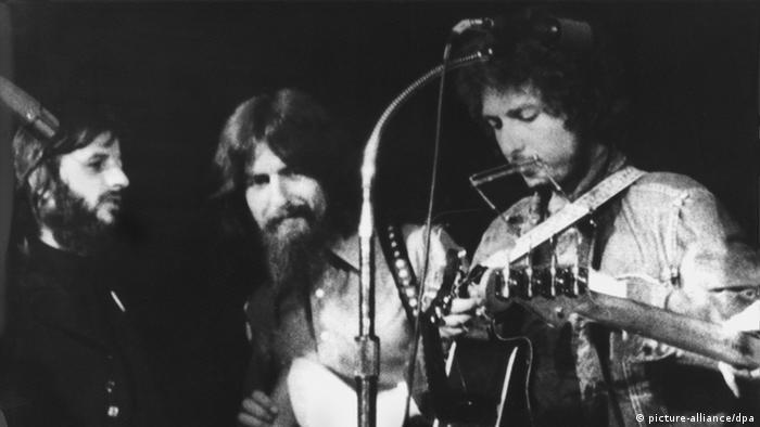 باب دیلن (راست) در کنار جرج هریسون (وسط) و رینگو استار از گروه بیتلها در کنسرتی خیریه در بنگلادش در سال ۱۹۷۱