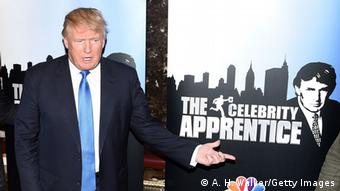 Donald Trump stands next to a 'Celebrity Apprentice' poster
