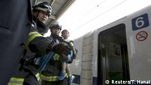 30.06.2015 **** A boy is carried by firefighters as he gets off a Shinkansen bullet train at Odawara station after it made an emergency stop, in Odawara, west of Tokyo June 30, 2015. Two passengers on a Japanese Shinkansen bullet train died after one doused himself in oil and set himself ablaze on Tuesday, media reports said. The train, carrying about 1,000 passengers, made an emergency stop on its way from Tokyo to the western city of Osaka after smoke started to fill at least one carriage, fire department officials said. A fire department official confirmed that one man was dead. Kyodo news agency, quoting a witness, identified him as the man who had covered himself with oil and set fire to himself. REUTERS/Toru Hanai