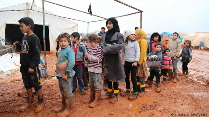 Syrian children stand in a line waiting for groceries in Idlib (Foto: Abacapress)