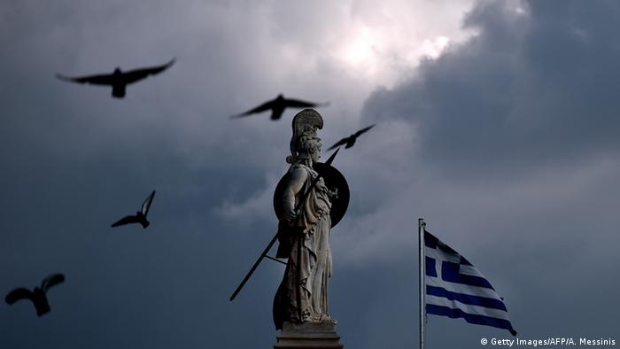 A Greek flag flies next to a statue of the ancient Greek goddess Athena