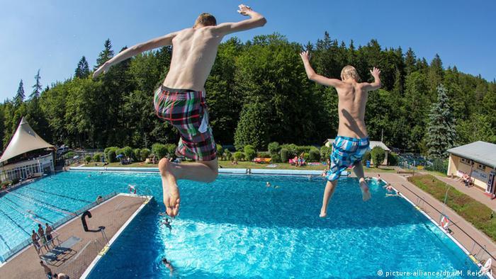 Zwei junge Männer springen von hoch oben in ein Freibadschwimmbecken