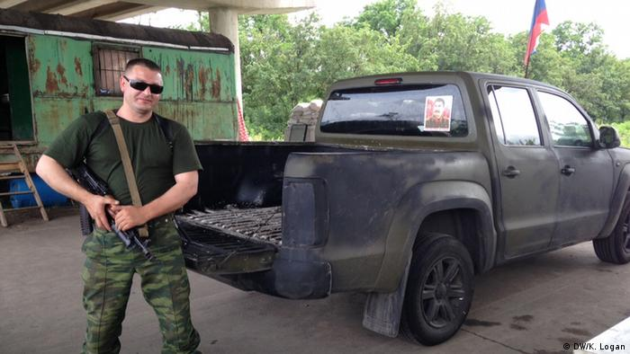 Sergei stands in front of his truck. A Stalin poster is taped to the back window