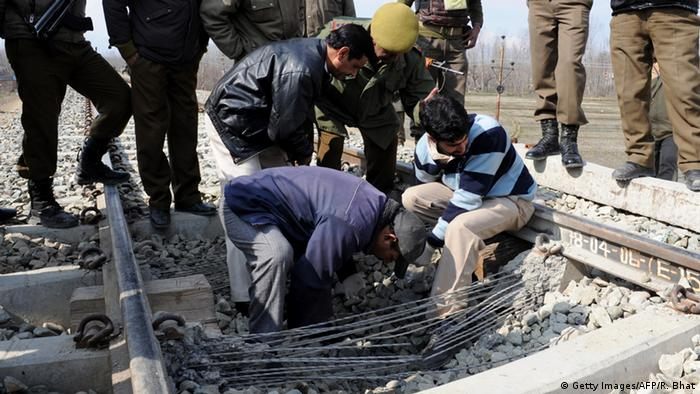 Indian police officers and forensic experts inspect a section of damaged railway track, which was the target of an explosion detonated by suspected militants at Kanipora Nowgam on the outskirts of Srinagar on March 8, 2011 (Photo: ROUF BHAT/AFP/Getty Images)