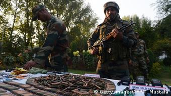 Indian troops display arms and ammunition captured from suspected militants after a gun battle in the Keran sector at the Line of control (LOC) in Srinagar on October 7, 2013 (Photo credit should read TAUSEEF MUSTAFA/AFP/Getty Images)