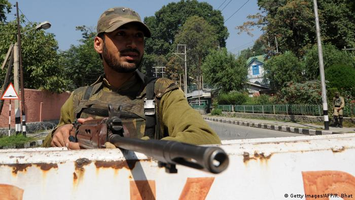 An Indian policemen stands guard as they block road along the way to the United Nations Military Observer Group in India and Pakistan.