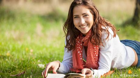 Eine junge Frau liegt auf der Wiese und liest ein Buch.
