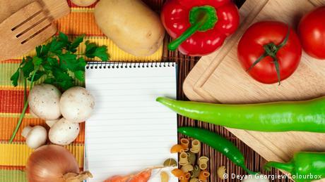 Frisches Gemüse auf einem Tisch, dazwischen ein Notizblock.