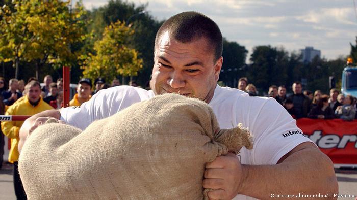 Ein kräftiger Mann hebt einen schweren Sack bei einem Wettkampf