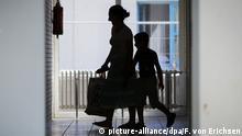 Während eine Gruppe Journalisten zusammen mit der rheinland-pfälzischen Integrationsministerin am 01.07.2015 die neue Aufnahmeeinrichtung für Asylbegehrende (AfA) in Ingelheim (Rheinland-Pfalz) besucht, laufen Asylbewerber über die Flure der Einrichtung. Die AfA Ingelheim wird zur eigenständigen Erstaufnahmeeinrichtung und bietet künftig Platz für rund 550 Menschen. Nach bis zu drei Monaten in einer AfA werden die Asylbewerber auf andere Kommunen verteilt. Rheinland-Pfalz rechnet in diesem Jahr mit rund 20 000 neuen Asylbewerbern. Foto: Fredrik von Erichsen/dpa pixel