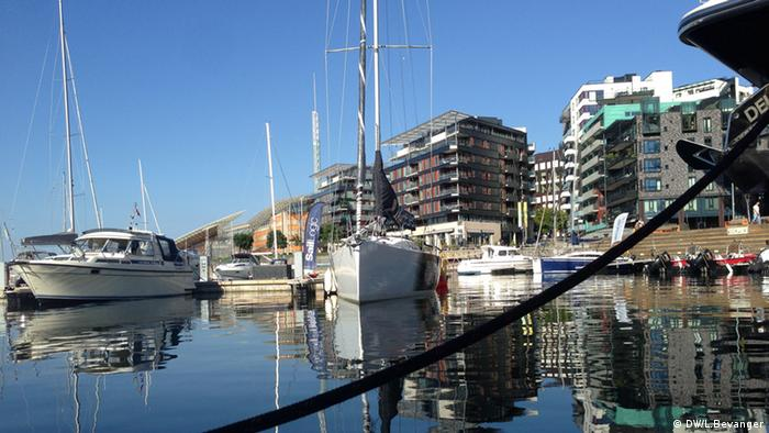 A picture of the harbor front in Oslo, Norway. Showing water, boats and appartments and a blue sky.