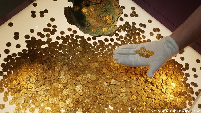 Hunderte alte Goldmünzen - der Trierer Goldschatz; eine Person mit weißen Handschuhen präsentiert sechs davon auf der Handfläche