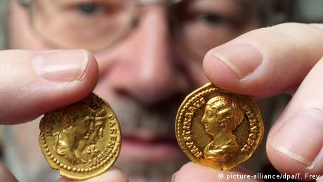 A man holds up two gold Roman-era coins from the Rhineland State Museum collection in Trier