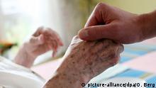 ARCHIV - Ein Pfleger hält im Alten-und Pflegeheim Joachim-Neander-Haus der Diakonie in Düsseldorf die Hand einer Bewohnerin (Foto vom 13.11.2007). Foto: Oliver Berg/dpa (zu dpa-Hintergrund Internationale Regelungen zur Sterbehilfe vom 24.01.2014) +++(c) dpa - Bildfunk+++