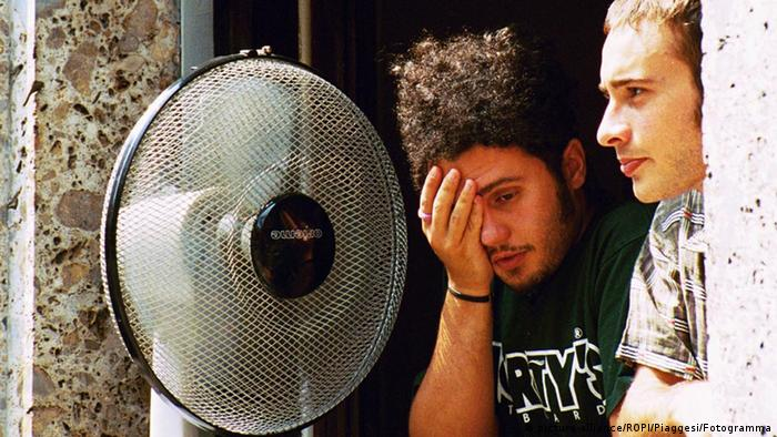 Люди возле вентилятора спасаются от жары