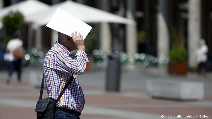 A man tries to shield himself from the sun in Valladolid, Spain