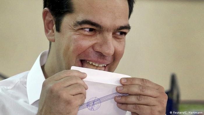 Greek Prime Minister Alexis Tsipras licks his ballot envelope before voting at a polling station in Athens, Greece July 5, 2015