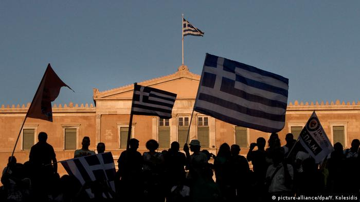 People waving Greek flags outside parliament