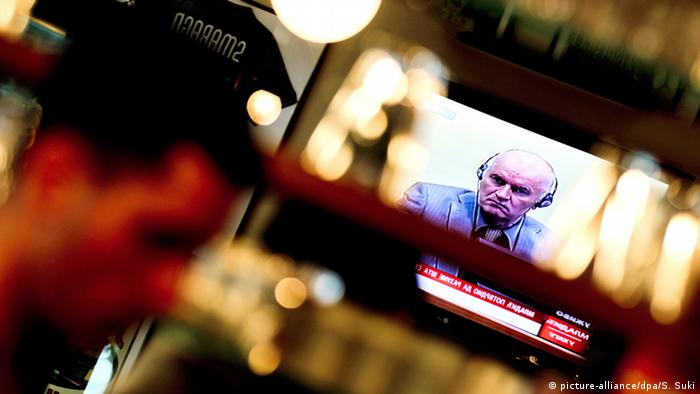 People watch a live TV broadcast of Ratko Mladic appearing at the Hague war crimes tribunal