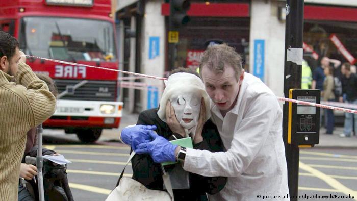 Ein Helfer begleitet eine verletzte Frau aus der U-Bahn-Station nach den Anschlägen in London 2005. (Foto: dpa)