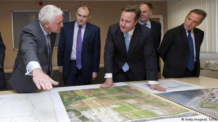 (L-R) Nigel Cann site director of Hinkley Point Site C, who was then UK Secretary for Energy and Climate Change Ed Davey, ex-Prime Minister David Cameron, Vincent de Rivaz, ex-Chief Executive of EDF and Henri Proglio, ex-CEO and Chairman of EDF, examine site plans for Hinkly C nuclear power station at Hinkley Point in October 2013.
